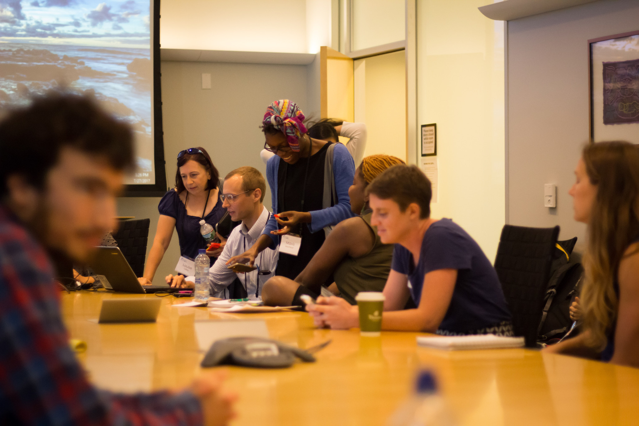 Group of graduate students sitting and talking at conference table with a large projection screen in the background.
