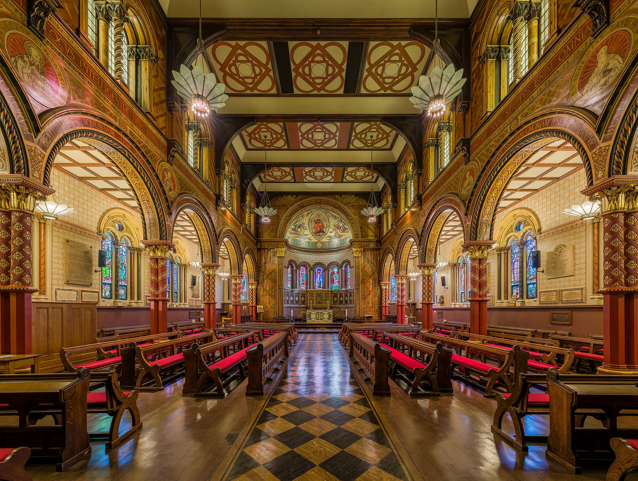 An elaborate room in King's College London with carved wooden arches and inlaid parquet floors